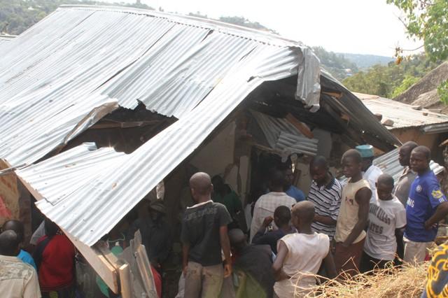 Baadhi ya wakazi wa Mwanza wakiangalia nyumba iliyoporomokewa na mwamba katika Mtaa wa Nyerere A Sinai-Mabatini jana.