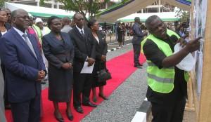 Rais Dk. John Magufuli akimsikiliza Mtendaji Mkuu wa Wakala wa Majengo (TBA), Elius Mwakalinga, alipokuwa akielezea ujenzi wa hosteli za wanafunzi wa Chuo Kikuu cha Dar es Salaam (UDSM) baada ya kuweka jiwe la msingi jana. Kushoto kwake ni Waziri wa Elimu, Sayansi, Teknolojia na Mafunzo ya Ufundi, Profesa Joyce Ndalichako, Makamu Mkuu wa Chuo wa UDSM, Profesa Rwekaza Mukandala.