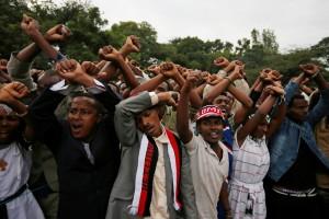 Demonstrators chant slogans while flashing the Oromo protest gesture during Irreecha, the thanksgiving festival of the Oromo people, in Bishoftu town, Oromia region, Ethiopia