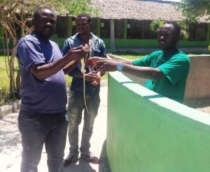 Mmoja wa watalii akijaribu kumshika nyoka kutoka kwa Mhifadhi, Nesto Hassan wa Kaole.